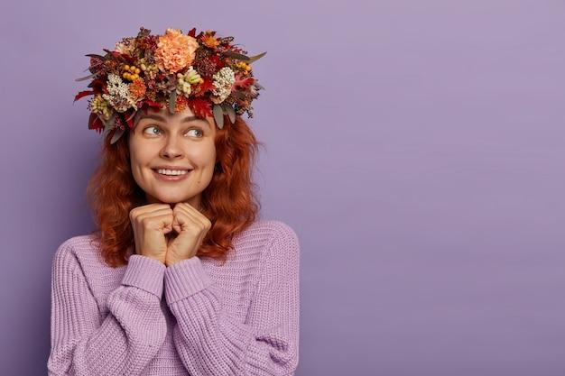 A garota feliz e sexy mantém as mãos embaixo do queixo, relembra um momento comovente, olha de lado com um sorriso cheio de dentes, se alegra fazendo grinalda de folhas de outono