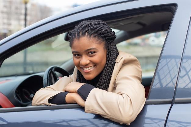 A garota feliz em um carro dirigindo, afro-americana