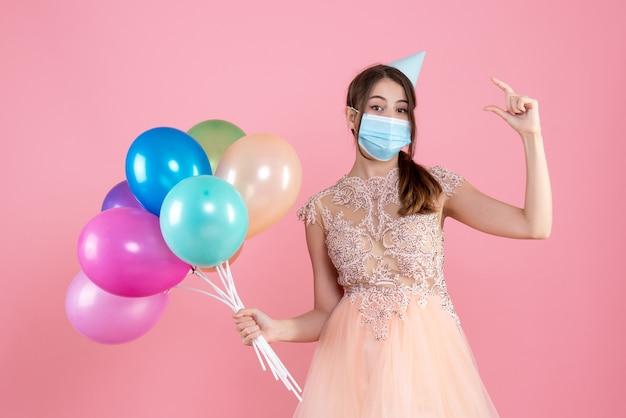 A garota fofa da festa com chapéu de festa e máscara médica com balões coloridos