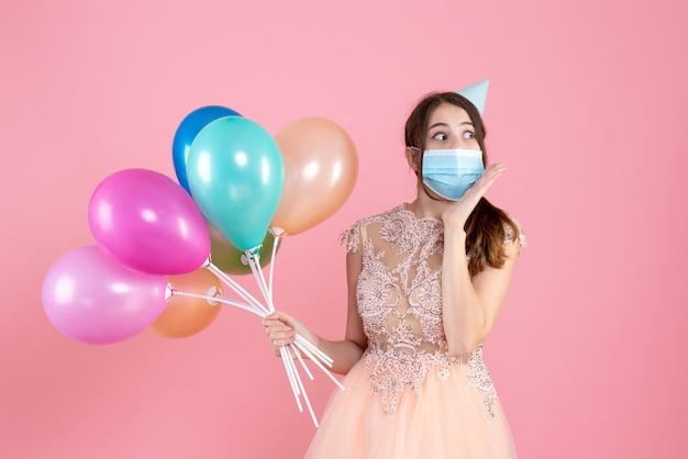 A garota fofa de vista frontal com tampa de festa segurando balões coloridos olhando para a direita