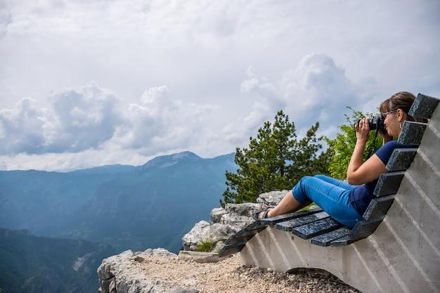 A garota fotógrafo está descansando no topo da montanha, sentado em um banco incomum.