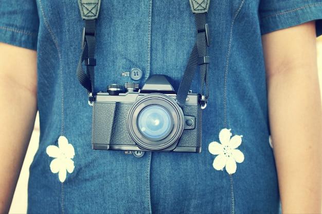 A garota hippie com pendurado a câmera sem espelho no tom retrô