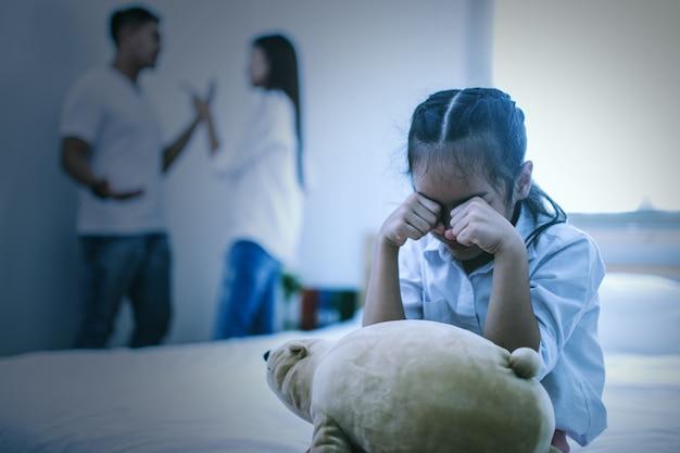 A garota infeliz sentada perto dos pais discutindo na cama