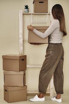 A garota inventa caixas de papel em uma prateleira de madeira. armazenamento e embalagem ecológicos.