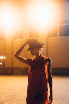 A garota jovem e atraente com um chapéu posa para a câmera à noite