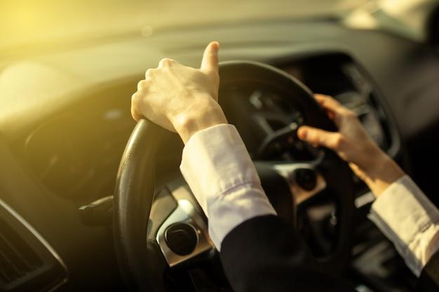 A garota mantém as mãos atrás do volante do carro