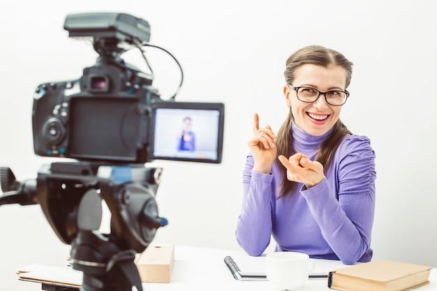 A garota mantém um blog gravando na câmera. uma mulher com óculos leva seu vlog