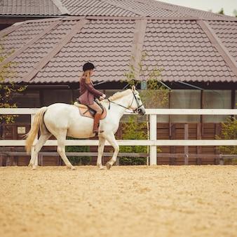 A garota monta um cavalo