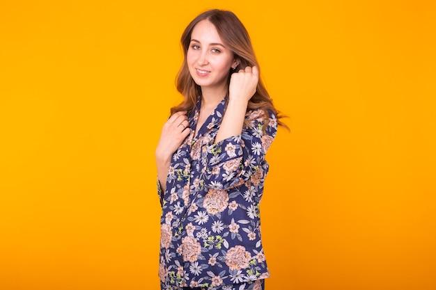 A garota muito legal do retrato da moda em casa usa pijama se divertindo com a parede amarela colorida.