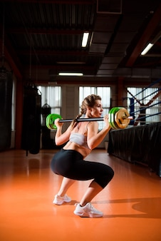 A garota na academia levanta o peso.