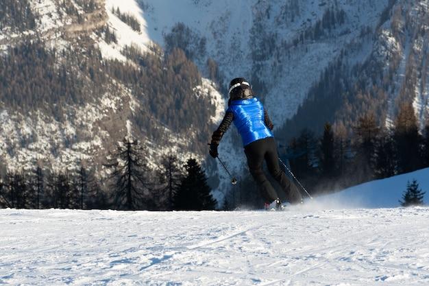 A garota na montanha de esqui na velocidade para baixo da encosta