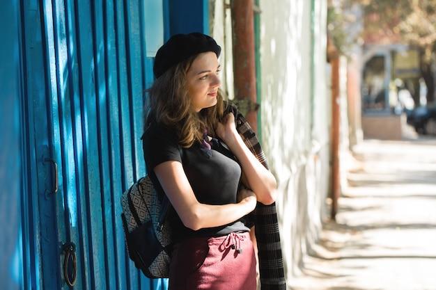 A garota na parede azul de boina e saia, francesa elegante na sombra da cidade
