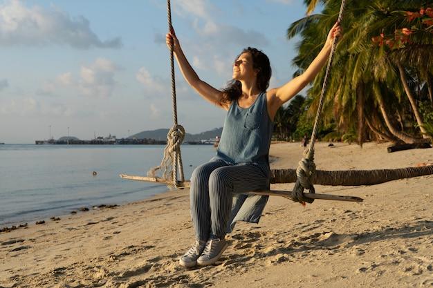 A garota na praia monta em um balanço durante o pôr do sol. pôr do sol nos trópicos, curtindo a natureza. balanço amarrado a uma palmeira pelo oceano