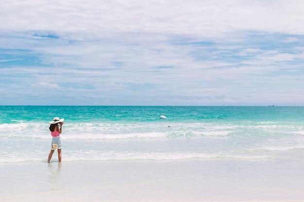 A garota na praia. os turistas estão tirando fotos por diversão.