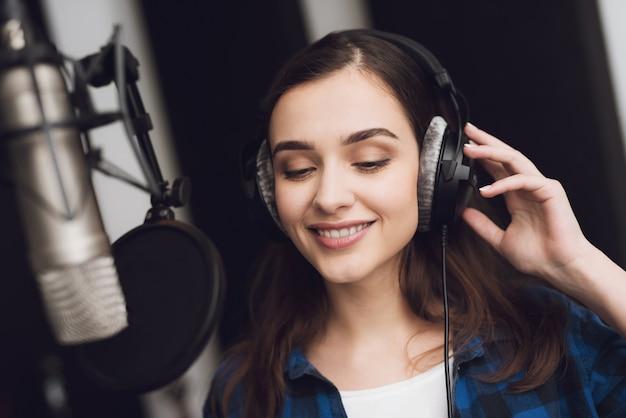 A garota no estúdio de gravação canta uma canção