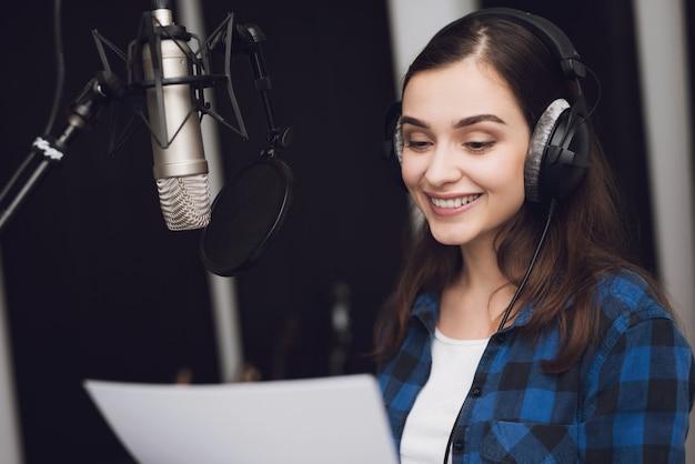 A garota no estúdio de gravação canta uma música.