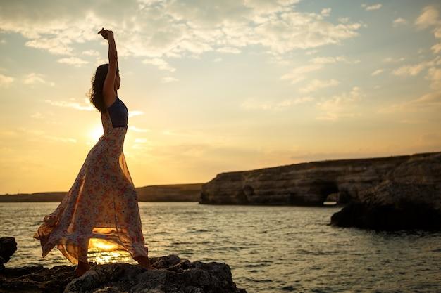 A garota no fundo de uma bela paisagem e pôr do sol, silhueta de uma menina em um penhasco, em um penhasco, lindo céu e mar