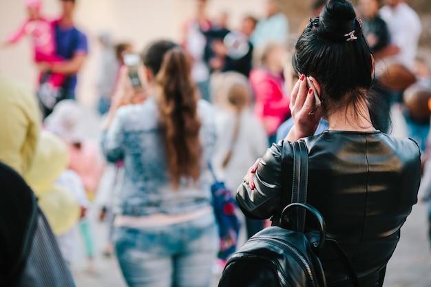A garota no meio da multidão usa o telefone. foto de rua