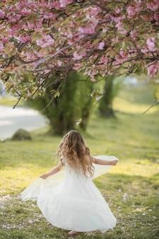 A garota no parque correndo e brincando vestida com longos vestidos brancos como uma noiva