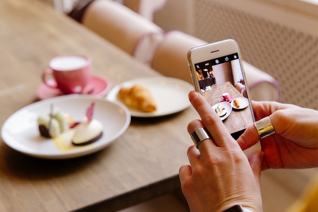 A garota no restaurante fotografando a comida no telefone.