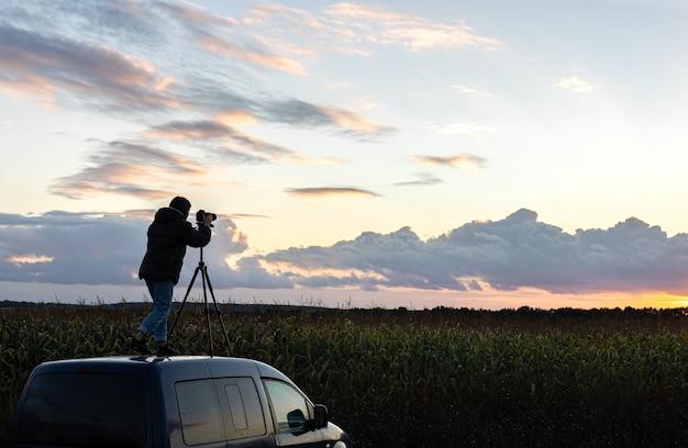 A garota no teto do carro fotografa o pôr do sol com um tripé.