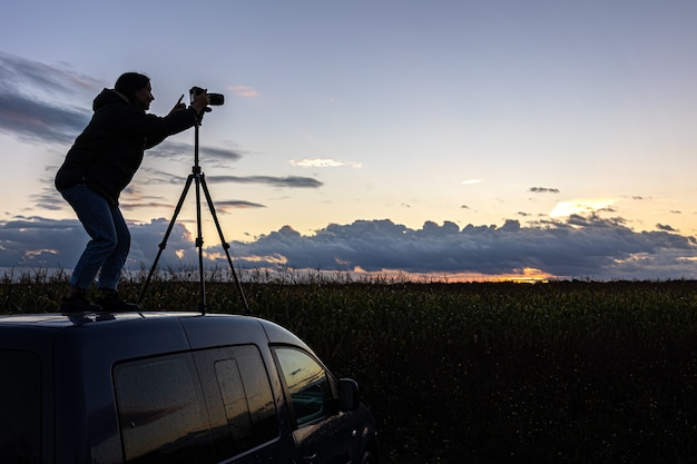 A garota no teto do carro fotografa o pôr do sol com um tripé