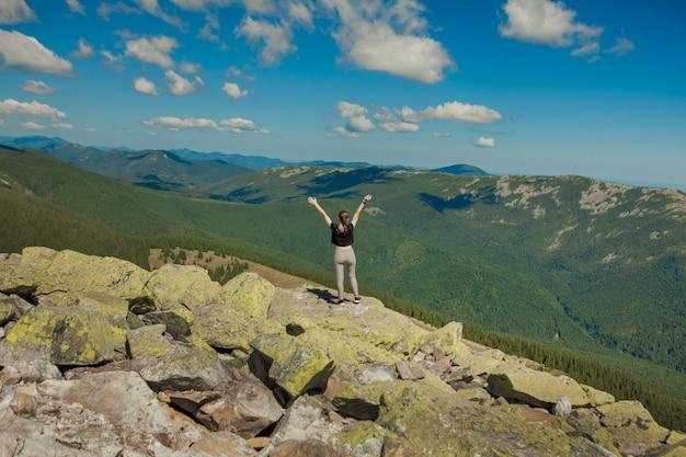 A garota no topo da montanha levantou as mãos. mountain view largo do verão no nascer do sol e na cordilheira distante coberta. beleza da natureza
