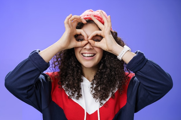 A garota nos vê como uma imitação de peek com binóculos fazendo círculos sobre os olhos e olhando através deles com alegria e empolgação, se divertindo, posando de feliz e fofa sobre um fundo azul em roupa ao ar livre.