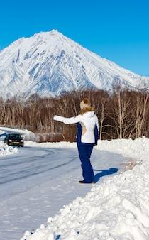 A garota pedindo carona na estrada do inverno
