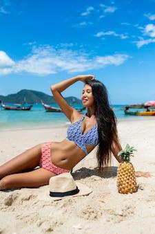 A garota perfeita sentada com praia de abacaxi. de viagem. lindo modelo feminino asiático com frutas tropicais. barco tailandês no