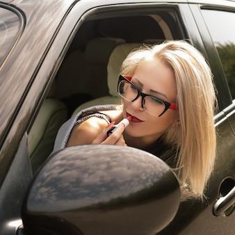 A garota pinta os lábios com batom vermelho se olha no espelho no protetor solar de seu carro