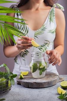 A garota prepara um verão e joga um pedaço de limão em um jarro