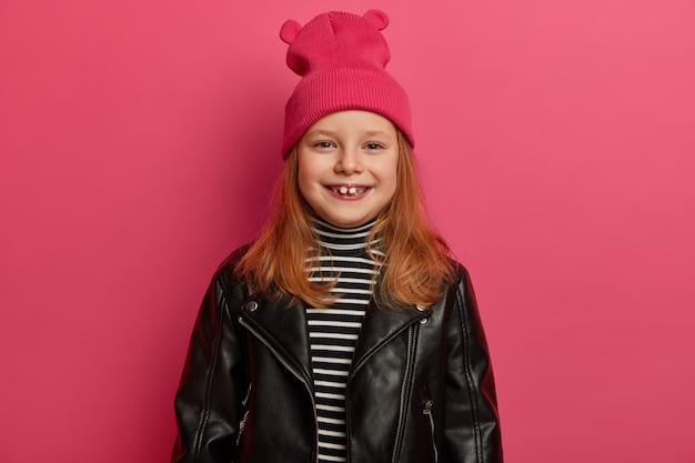 A garota ruiva elegante e positiva sorri amplamente, tem falta de dentes, veste uma jaqueta de couro da moda e um chapéu rosa, gosta de um dia bonito, passa o fim de semana com os pais, está de ótimo humor, posa dentro de casa