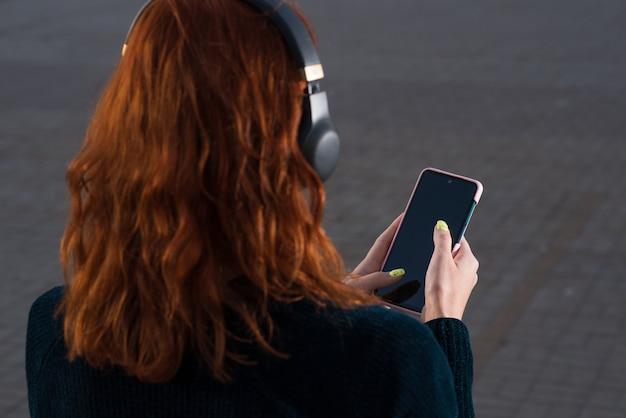 A garota ruiva em fones de ouvido, ouvindo música e usando um smartphone. vista traseira.