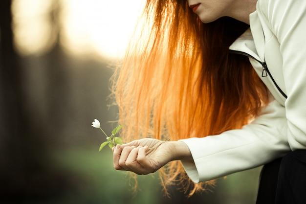 A garota ruiva está admirando a flor
