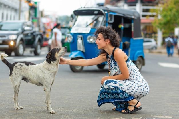 A garota se comunica com um cachorro vadio na rua. faça carinho no cachorro.
