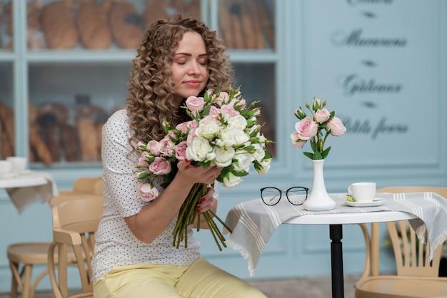 A garota se senta à mesa, segurando um buquê nas mãos e cheirando flores