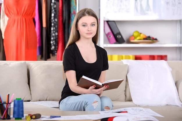 A garota se senta atrás de um livro e lê a casa.