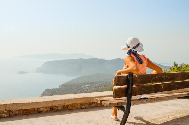 A garota se senta em um banco e desfruta de uma excelente vista do mar e das montanhas.
