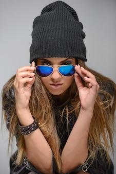 A garota se senta em um chapéu e óculos de sol.
