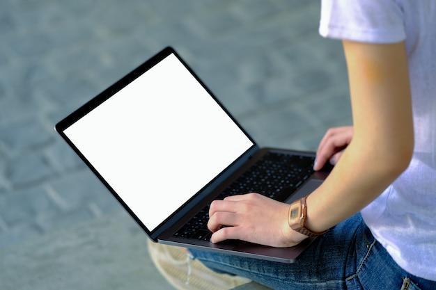 A garota se sentou no chão e usou um laptop branco em branco na perna.
