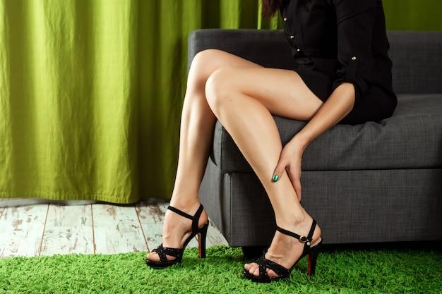 A garota segura as pernas, a dor nas pernas dos calcanhares