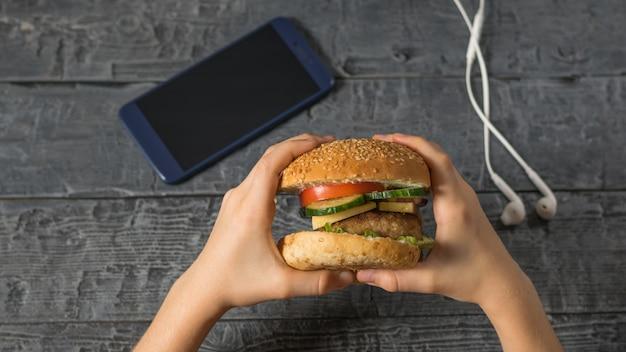 A garota segura um hambúrguer preparado sobre uma mesa com um telefone e fones de ouvido