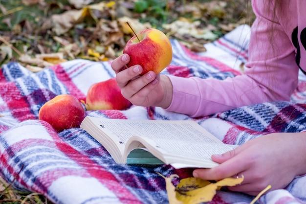 A garota segura uma maçã na mão e lê o livro. descanse na natureza no outono_