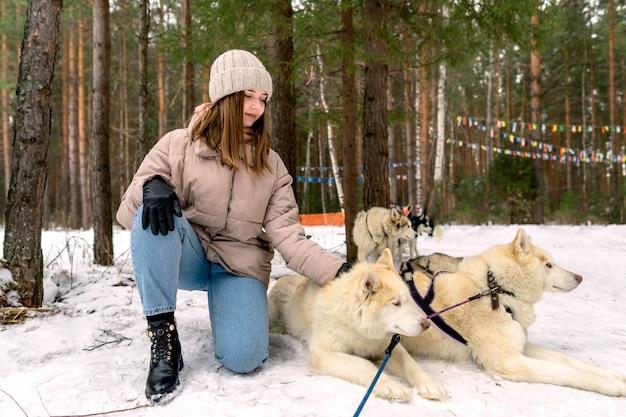 A garota senta-se ao lado de um husky siberiano branco e acaricia-a.