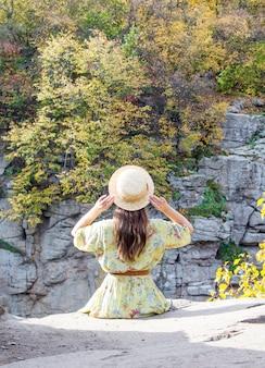 A garota senta-se na beira do canyon