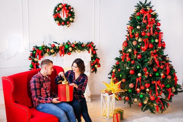 A garota sentada com o cara no sofá e abre o presente em uma sala aconchegante com lareira