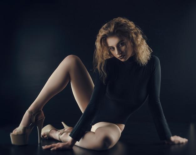 A garota sexy flexível posa em um fundo preto no baud de roupas adequadas