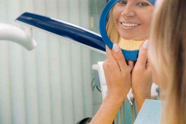 A garota sorri e se olha no espelho na odontologia