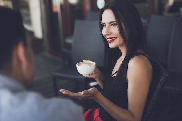 A garota sorri e segura uma caneca de cappuccino na mão